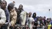 Migrants wait to disembark from the Italian Coast Guard ship Peluso, on the tiny Italian island of Lampedusa, Sunday, May 31, 2015. Around 75,000 migrants have been picked up trying to enter Italy and Greece from Libya so far this year. More than 1,800 are feared to have died. Most rescue emergencies happen some 40 nautical miles from Libya. (AP Photo/Mauro Buccarello)/LAM104/865121188143/1505311656